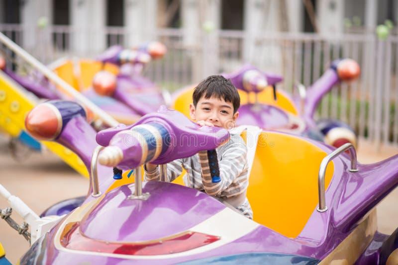 Rapaz pequeno no parque de diversões exterior fotos de stock royalty free