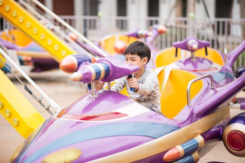 Rapaz pequeno no parque de diversões exterior fotos de stock