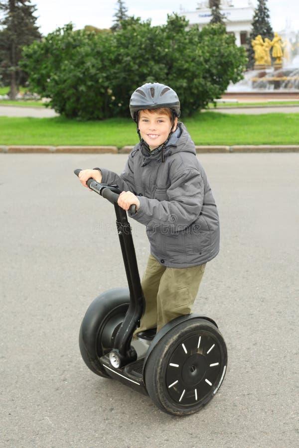 Rapaz pequeno no passeio do capacete em segway fotos de stock