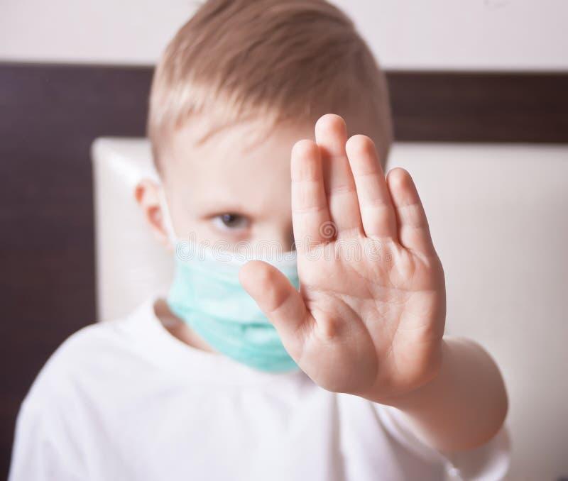 Rapaz pequeno no sinal da parada da exibição da máscara protetora com sua mão fotos de stock royalty free