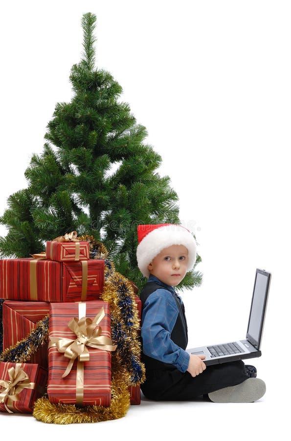 Rapaz pequeno no tampão de Santa Claus com um portátil e os presentes do Natal fotografia de stock