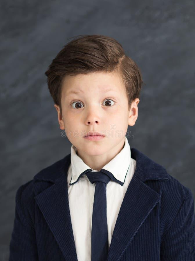 Rapaz pequeno no terno de negócio com expressão chocada imagem de stock