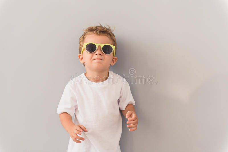 Rapaz pequeno nos óculos de sol que levantam no estúdio fotografia de stock