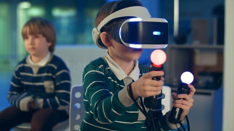 Rapaz pequeno nos auriculares do vr que jogam o jogo da realidade virtual com controladores quando um outro menino que espera sua foto de stock royalty free
