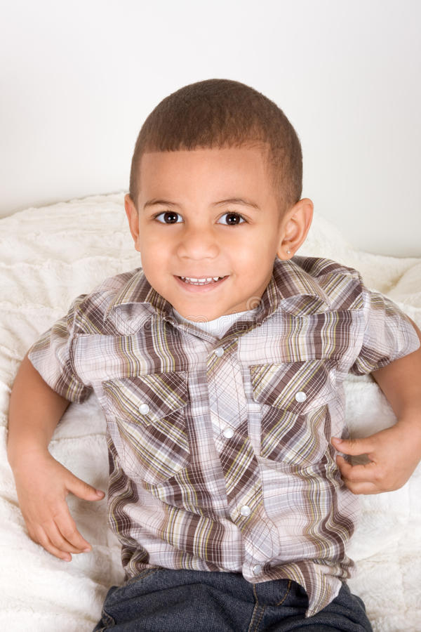 Rapaz pequeno novo em camisa e em calças de brim checkered imagem de stock
