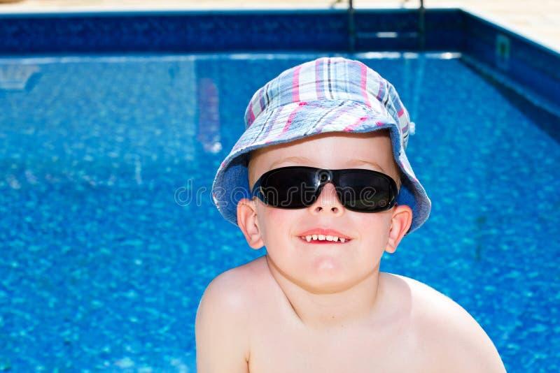 Rapaz pequeno oleado acima com creme do sol imagem de stock