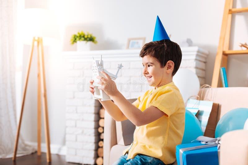 Rapaz pequeno otimista que examina seu brinquedo do robô do aniversário fotografia de stock royalty free