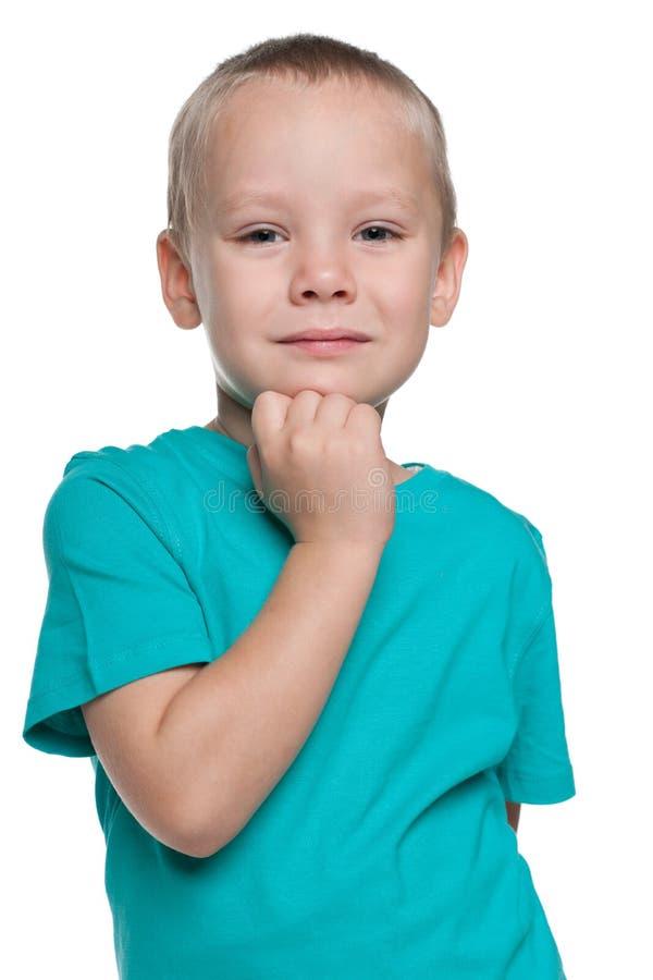 Rapaz pequeno pensativo em uma camisa azul fotos de stock royalty free