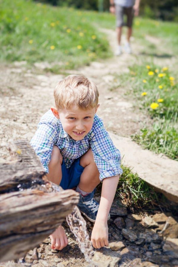 Rapaz pequeno perto do córrego claro da montanha foto de stock royalty free