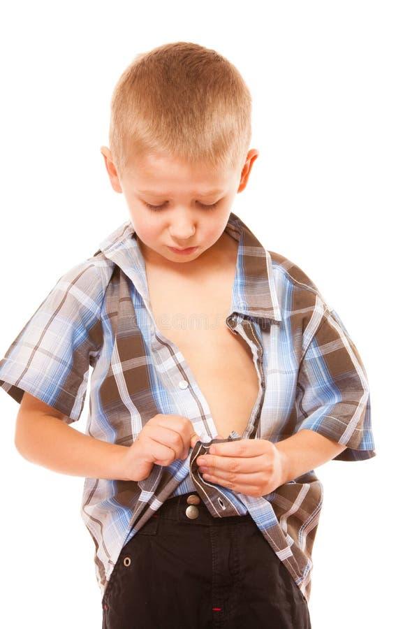 Rapaz pequeno que abotoa-se na camisa, isolada no branco fotos de stock