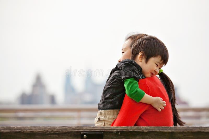 Rapaz pequeno que abraça a mamã no banco imagens de stock royalty free