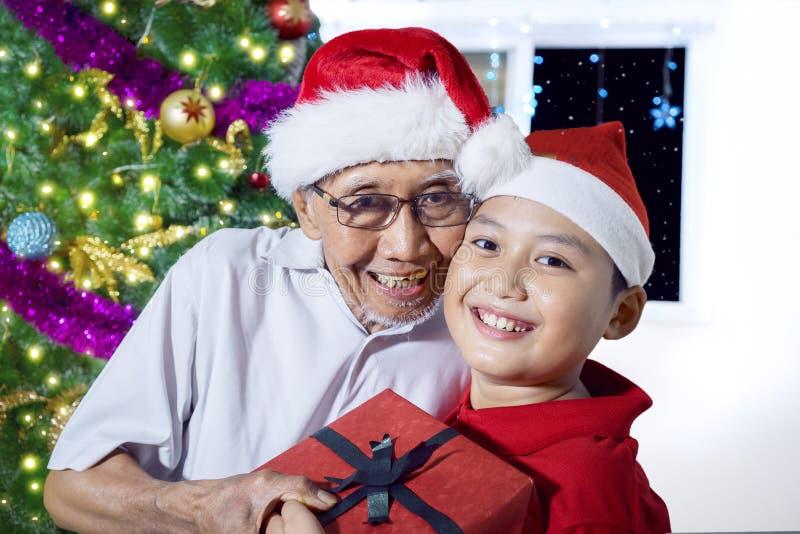 Rapaz pequeno que abraça seu avô no tempo do Natal fotos de stock royalty free