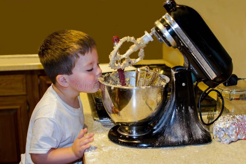 Rapaz pequeno que ajuda a cozer cookies fotos de stock royalty free