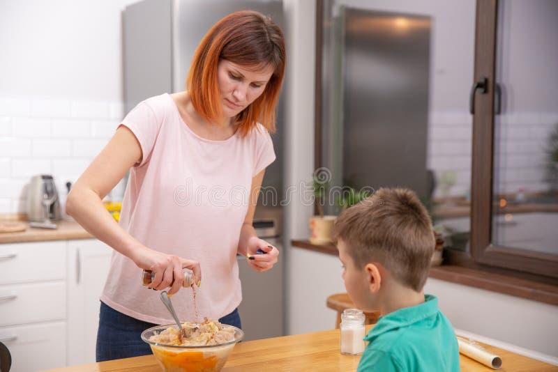 Rapaz pequeno que ajuda sua mãe com o cozimento na cozinha foto de stock royalty free