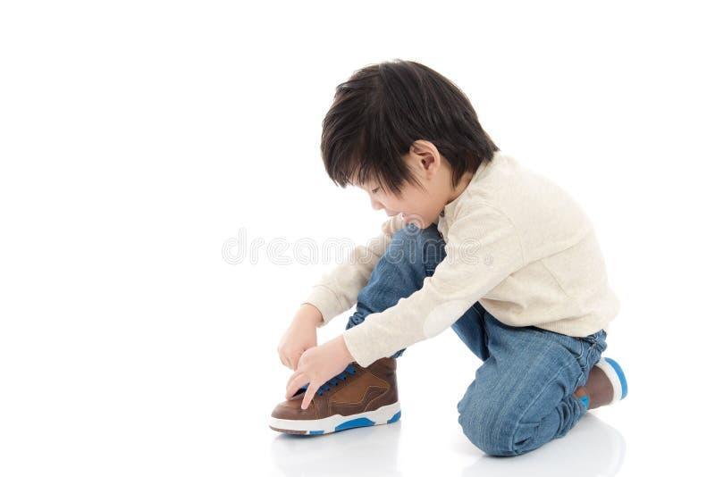 Rapaz pequeno que amarra suas sapatas no branco foto de stock royalty free