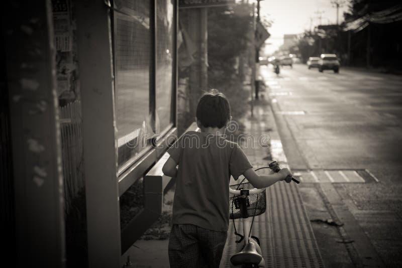 Rapaz pequeno que anda com a bicicleta na rua preto e branco imagens de stock