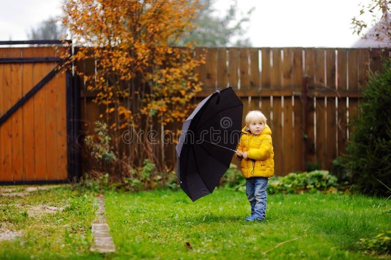 Rapaz pequeno que anda no tempo nebuloso chuvoso do outono foto de stock royalty free