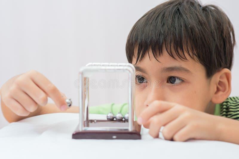 Rapaz pequeno que aprende a bola do equilíbrio do newton para o physic da ciência imagens de stock