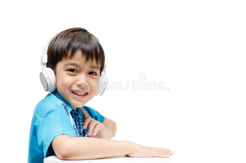Rapaz pequeno que aprende com os auriculares na orelha fotos de stock