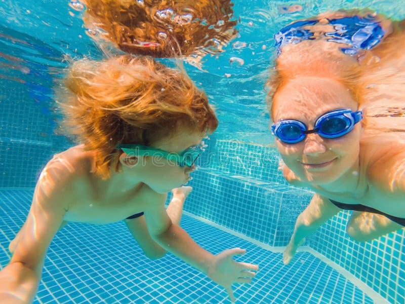 Rapaz pequeno que aprende nadar em uma piscina, mãe que guarda a criança fotografia de stock royalty free