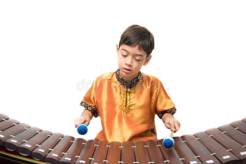 Rapaz pequeno que aprende o xilofone tailandês do instument, Ranat, no fundo branco imagem de stock royalty free