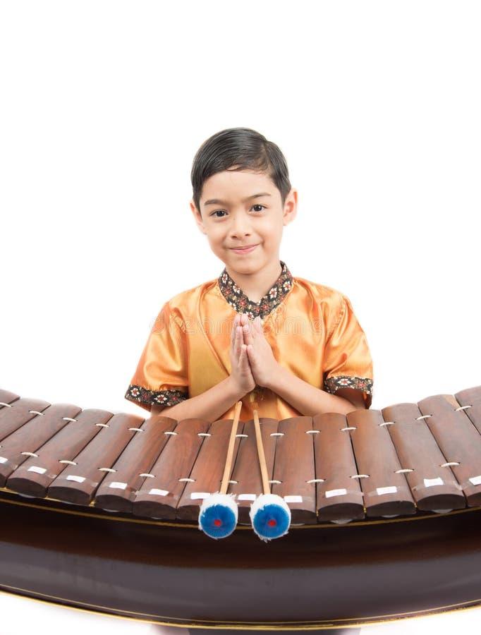 Rapaz pequeno que aprende o xilofone tailandês do instument, Ranat, no fundo branco fotografia de stock royalty free