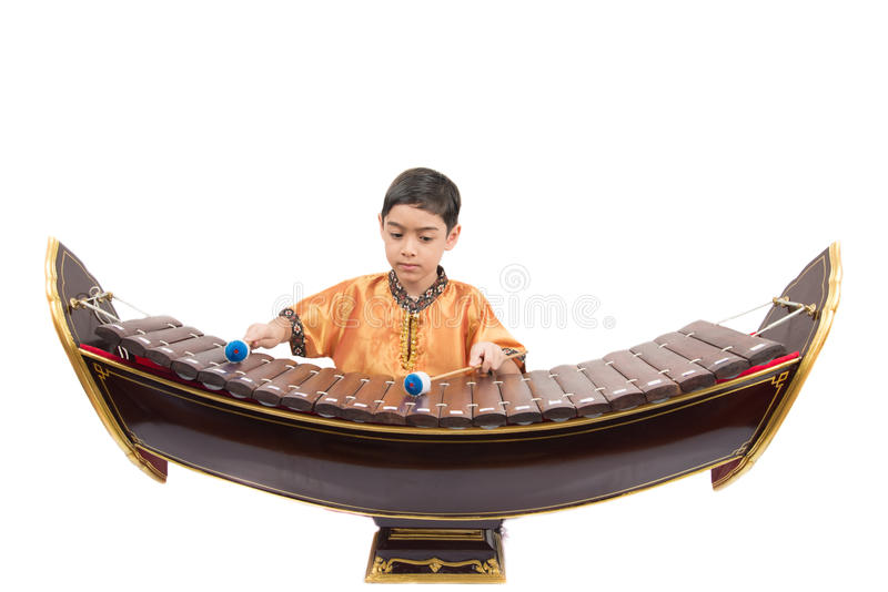Rapaz pequeno que aprende o xilofone tailandês do instument, Ranat, no fundo branco fotos de stock