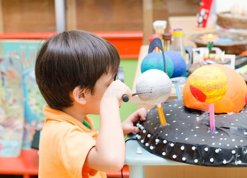 Rapaz pequeno que aprende a vista no espaço na classe fotos de stock royalty free