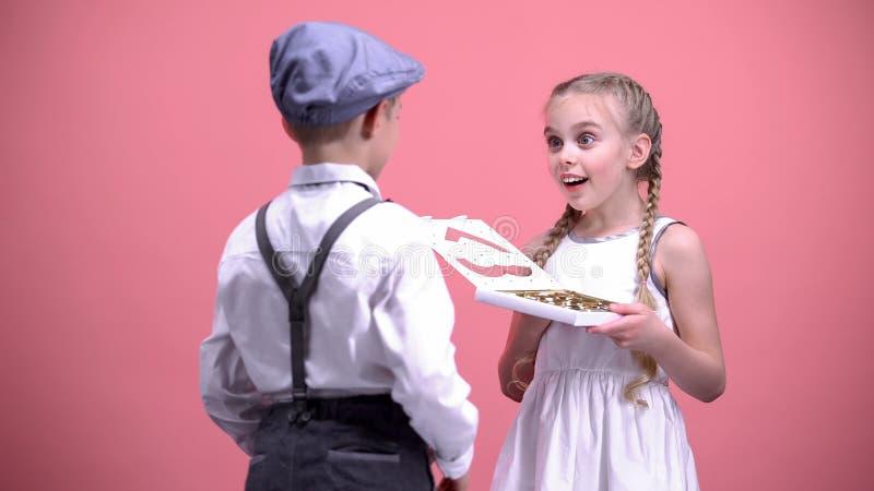 Rapaz pequeno que apresenta doces de chocolate à amiga surpreendida, dia de Valentim fotografia de stock