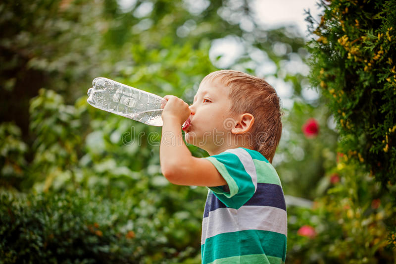 Rapaz pequeno que bebe a água mineral da garrafa plástica sobre para fora fotos de stock royalty free