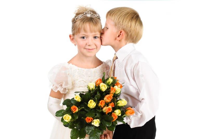 Rapaz pequeno que beija uma menina bonita imagens de stock royalty free