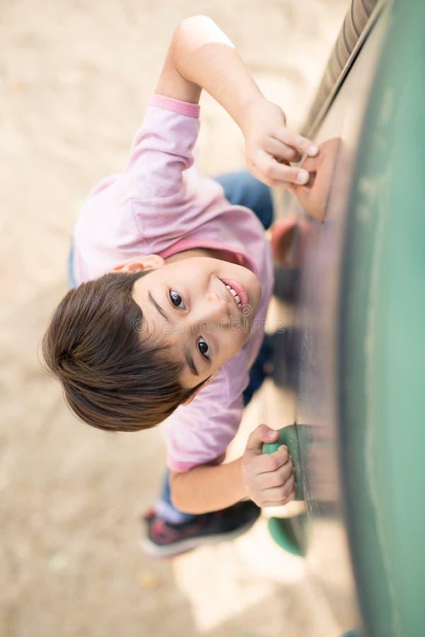Rapaz pequeno que climping acima do campo de jogos corajoso fotos de stock royalty free