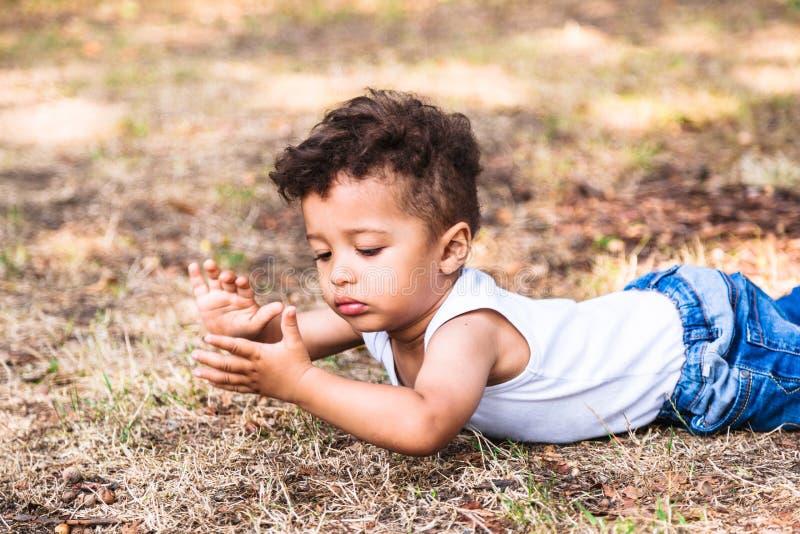 Rapaz pequeno que coloca na terra no parque exterior e que joga com mãos fotos de stock