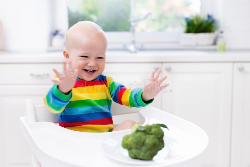 Rapaz pequeno que come brócolis na cozinha branca foto de stock