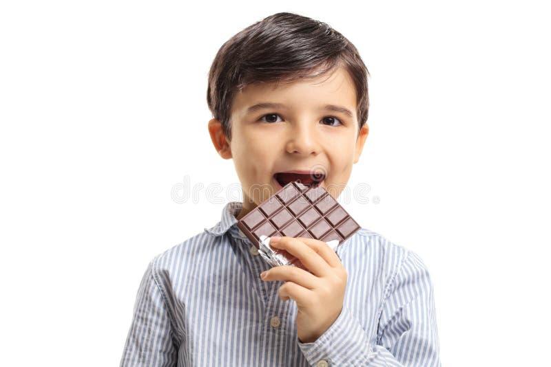 Rapaz pequeno que come o chocolate imagem de stock royalty free