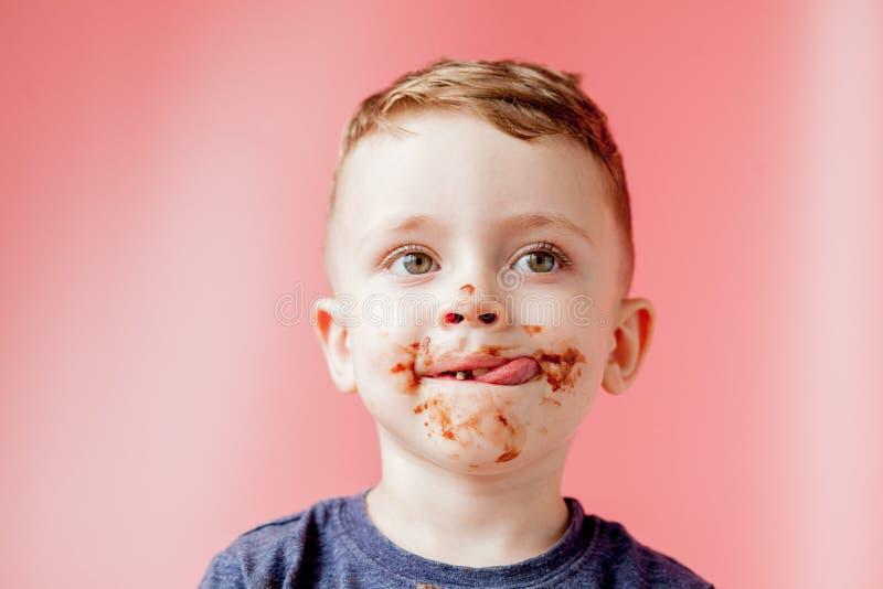 Rapaz pequeno que come o chocolate Menino feliz bonito manchado com o chocolate em torno de sua boca Conceito da crian?a fotos de stock royalty free