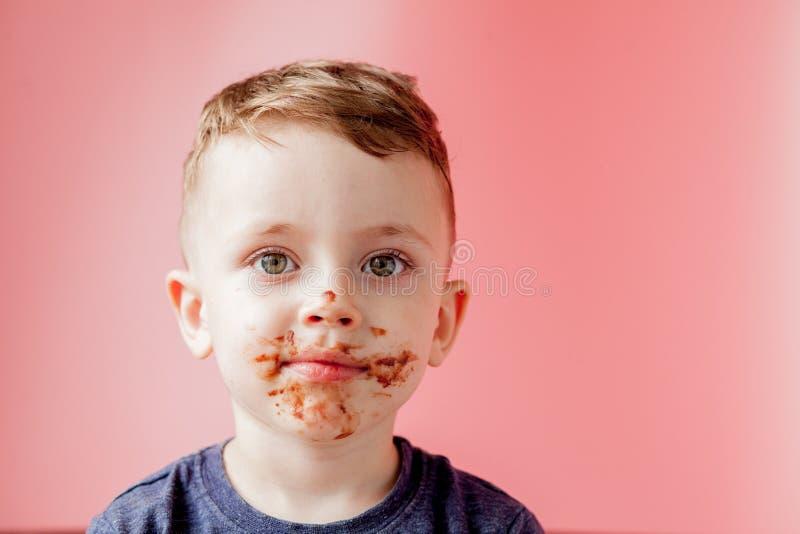 Rapaz pequeno que come o chocolate Menino feliz bonito manchado com o chocolate em torno de sua boca Conceito da crian?a imagem de stock royalty free