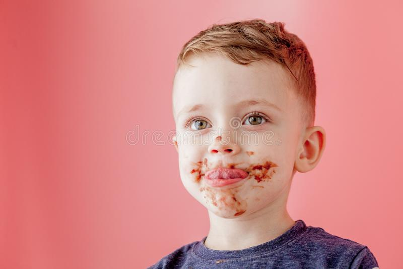 Rapaz pequeno que come o chocolate Menino feliz bonito manchado com o chocolate em torno de sua boca Conceito da crian?a imagens de stock