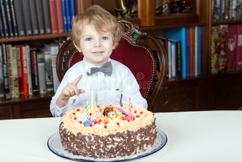 Rapaz pequeno que comemora o terceiro aniversário e que purga velas fotografia de stock