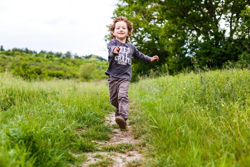 Rapaz pequeno que corre abaixo de um prado em uma paisagem bonita no verão, na cena muito clara e feliz Criança Curly imagem de stock