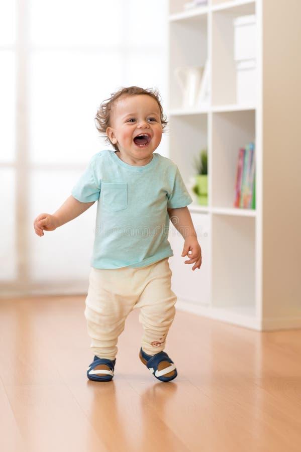 Rapaz pequeno que corre e que ri na sala de visitas do ther imagem de stock
