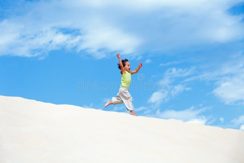 Rapaz pequeno que corre na duna de areia imagens de stock royalty free