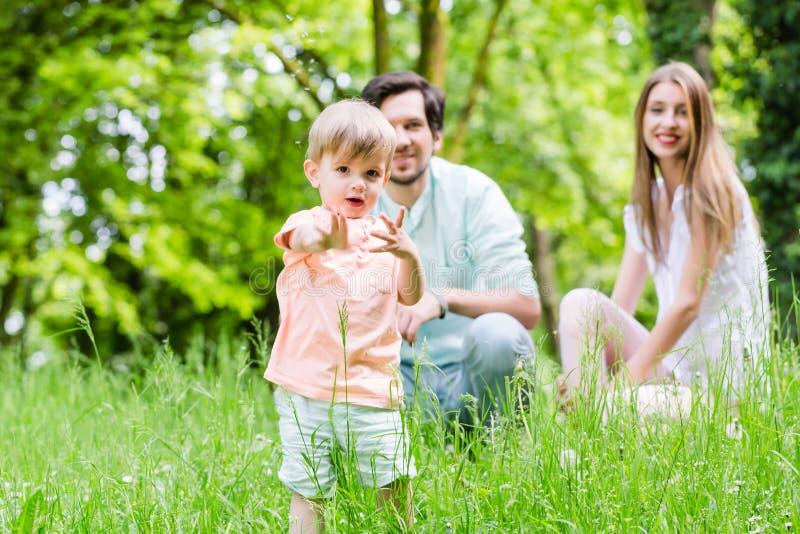 Rapaz pequeno que corre sobre o prado com família dentro para trás foto de stock royalty free
