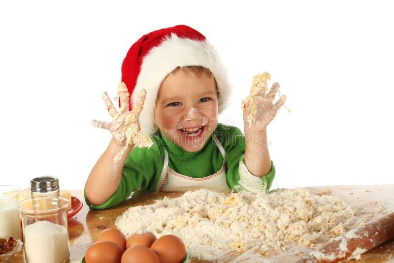 Rapaz pequeno que cozinha o bolo do Natal fotos de stock