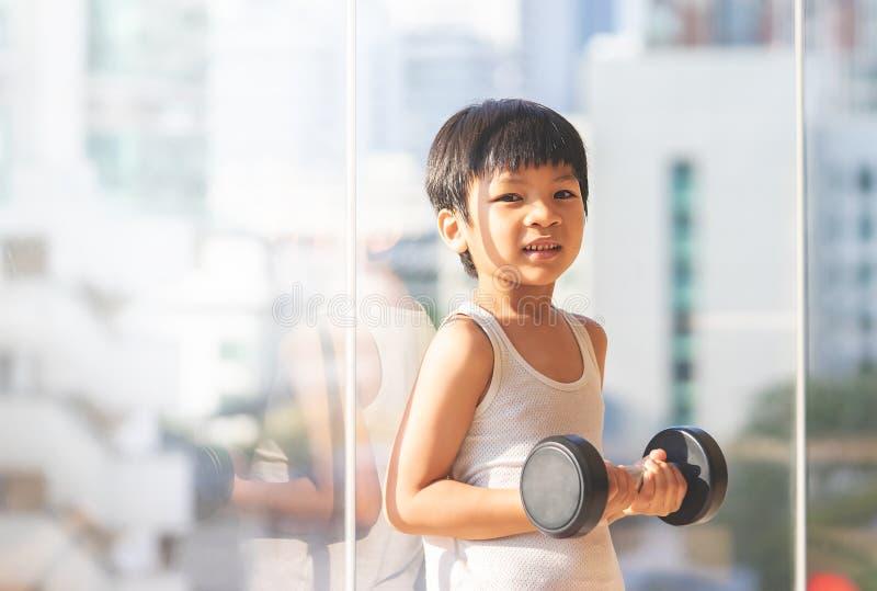 Rapaz pequeno que d? certo com peso pela cidade das janelas imagem de stock