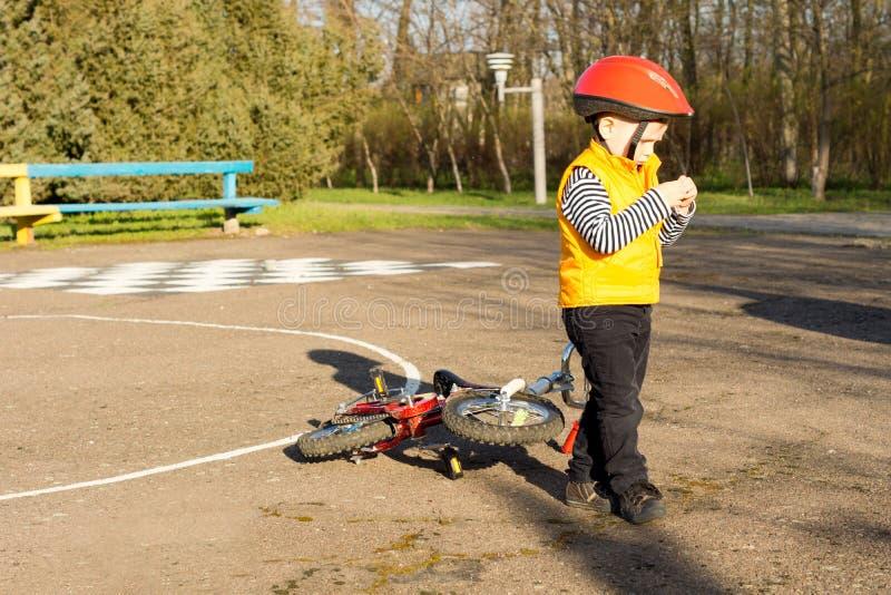 Rapaz pequeno que deixa sua bicicleta na borda da estrada imagens de stock royalty free