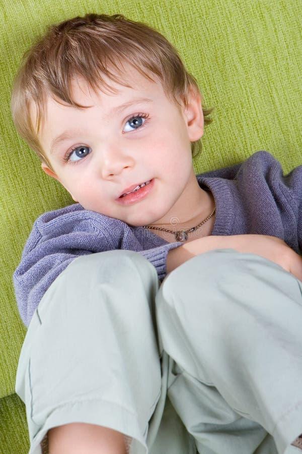 Rapaz pequeno que descansa em um sofá. fotos de stock royalty free