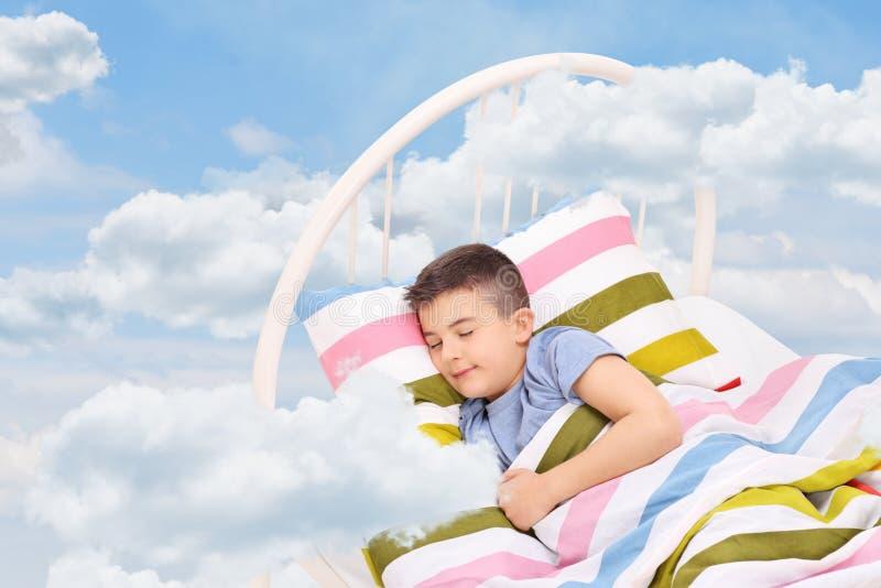 Rapaz pequeno que dorme em uma cama nas nuvens foto de stock royalty free