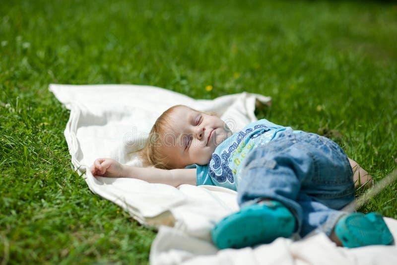 Rapaz pequeno que dorme em uma grama no verão fotografia de stock