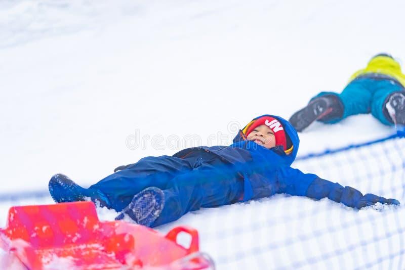 Rapaz pequeno que encontra-se para baixo na neve fotos de stock royalty free